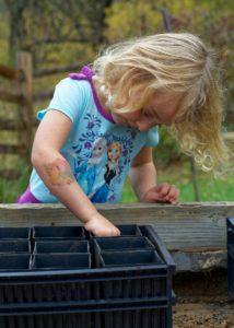 Young girl sowing seeds